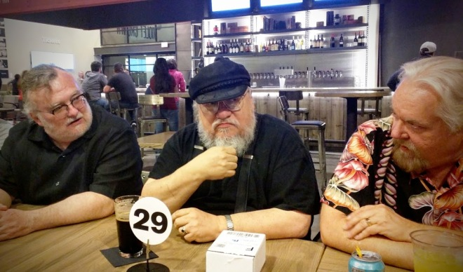 A candid of S.M. Stirling, George R. R. Martin, and Walter Jon Williams during the celebration after the panel